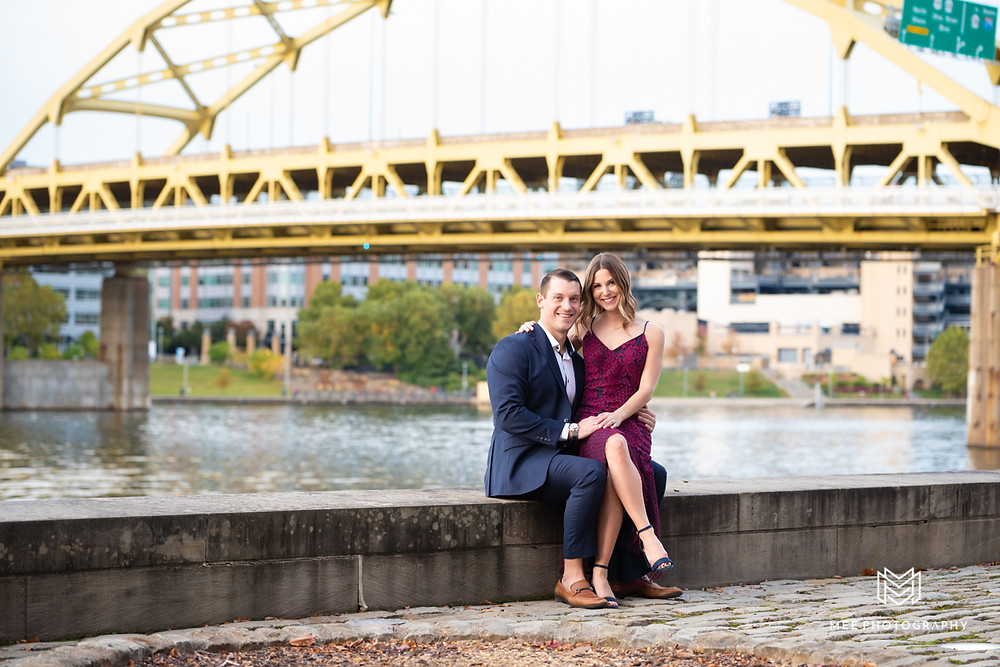 Couple sitting by the Ohio River with the Roberto Clemente bridge in the background; pittsburgh engagement