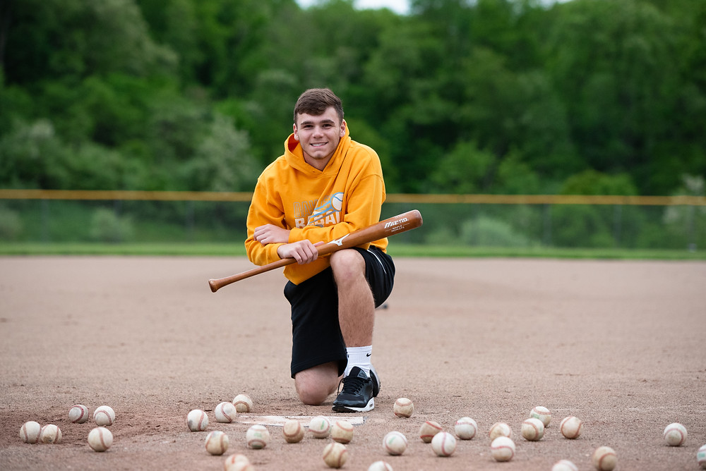 Senior guy baseball pictures at Oak Glen High School with baseballs scattered on the baseball field