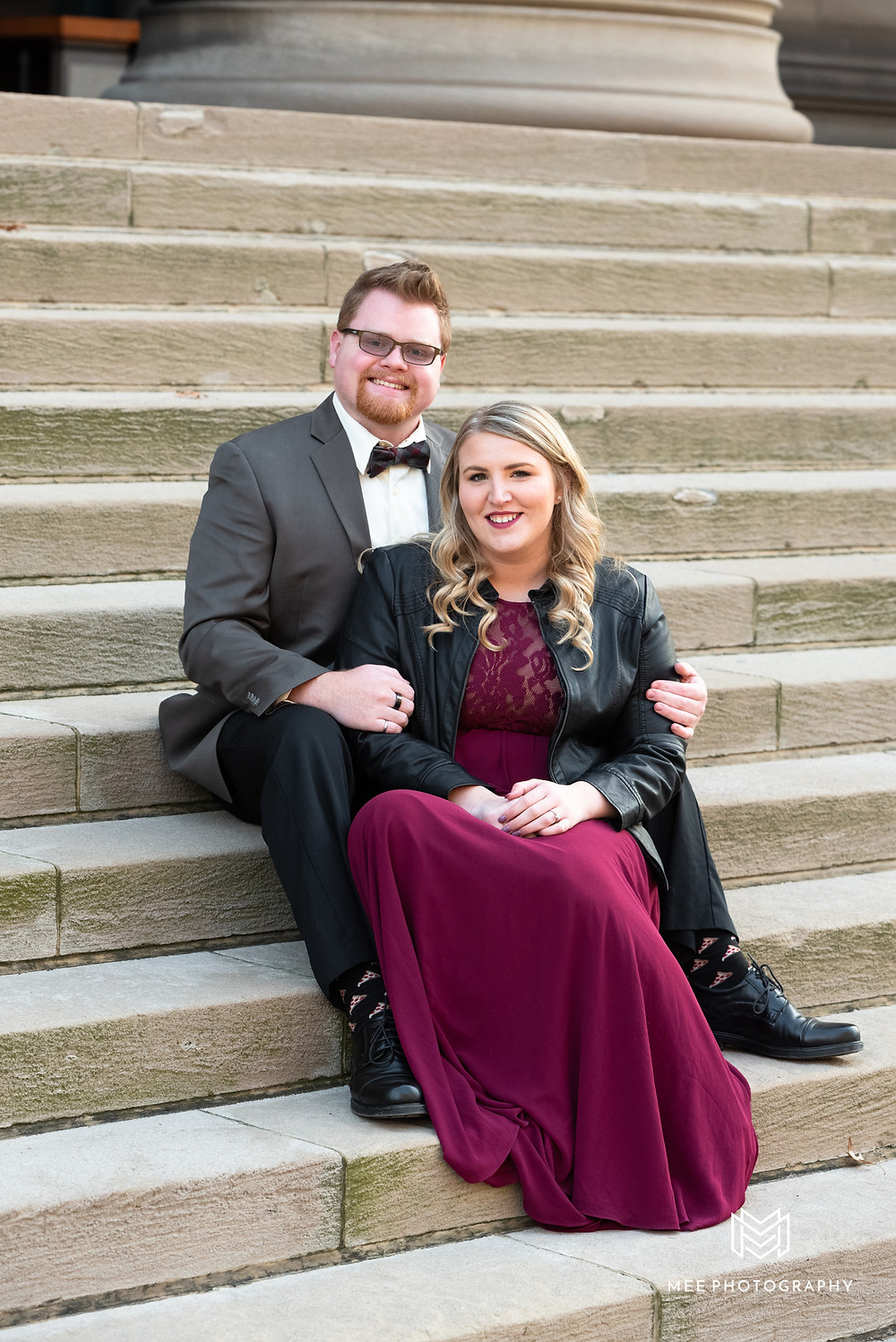 Portrait of a girl in burgudy dress and her fiance in a gray suit sitting on steps