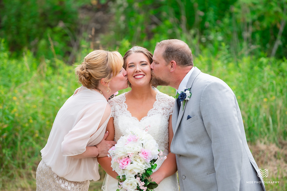 Mother and father of the bride kissing her on the cheek
