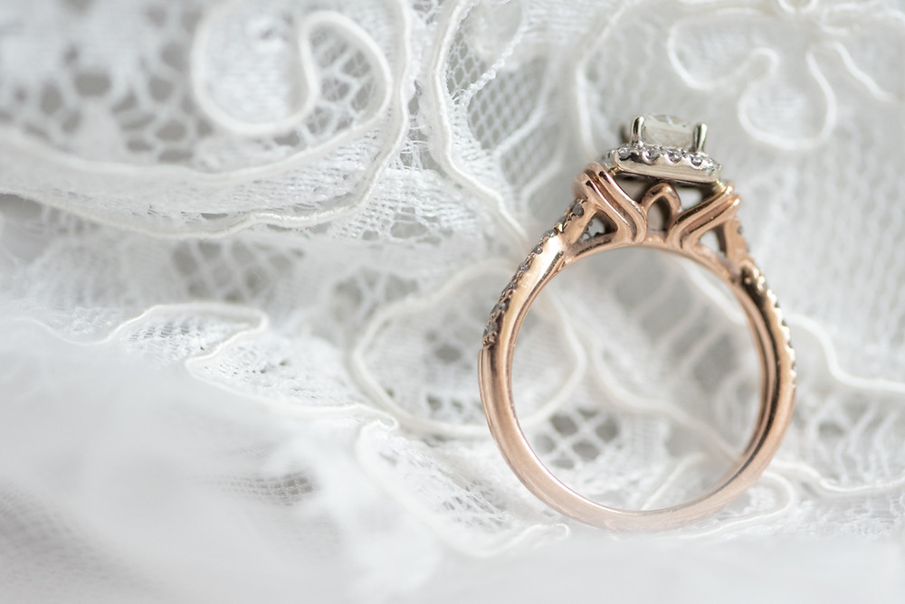 Rose gold diamond engagement ring sitting on a white lace wedding veil