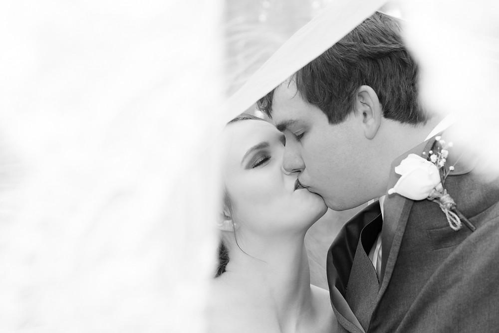 newlyweds kissing under veil