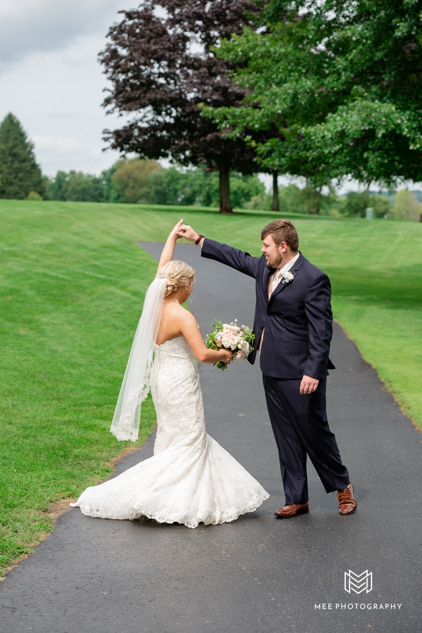 Groom spinning bride on golf course