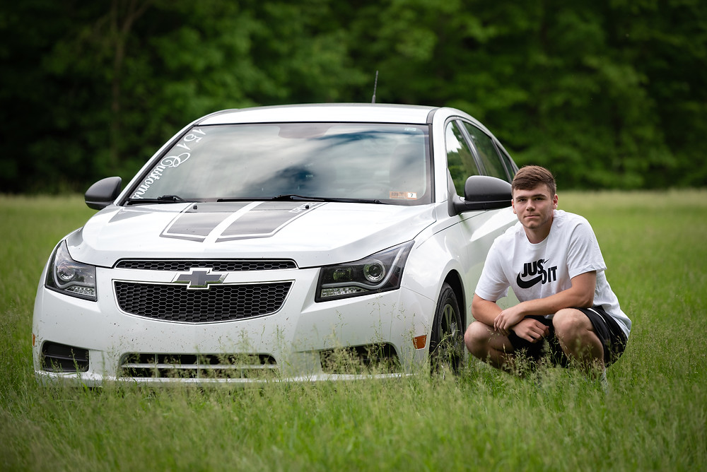 Senior crouched down next to his car in a field during his senior session at Tomlinson Run State Park