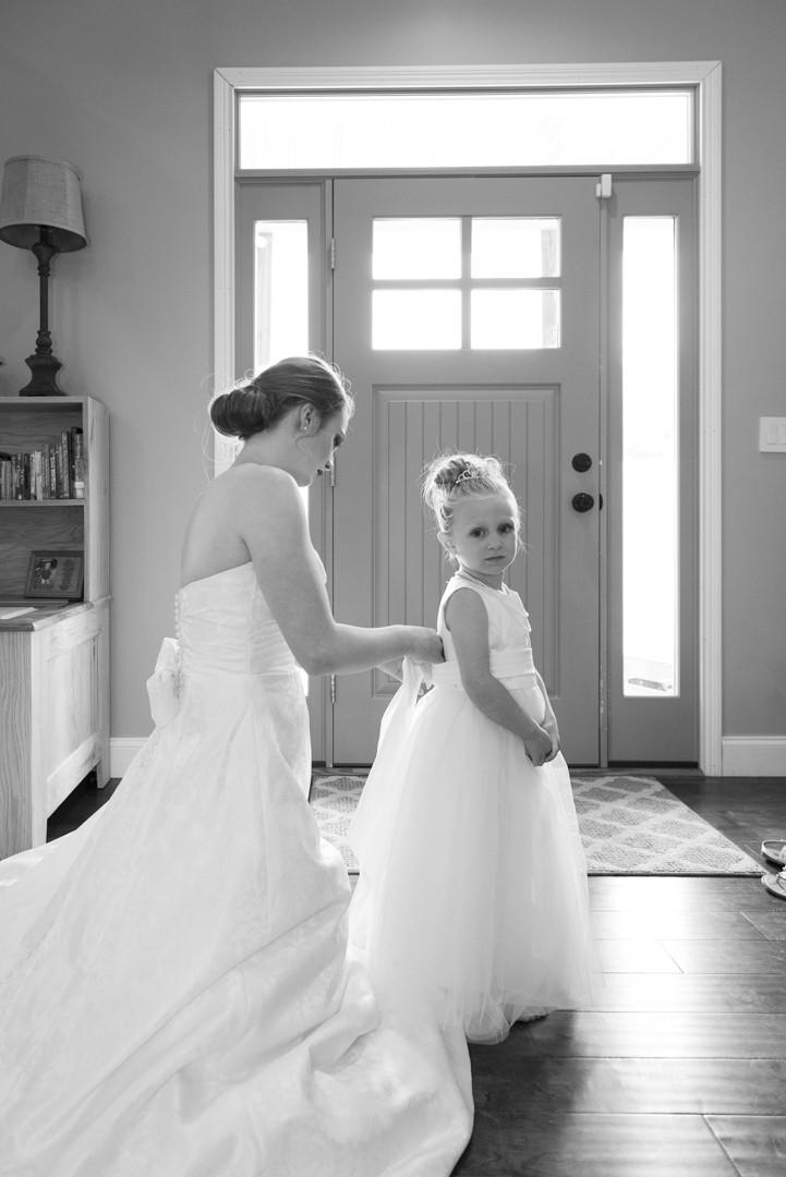 Bride helping flower girl get ready