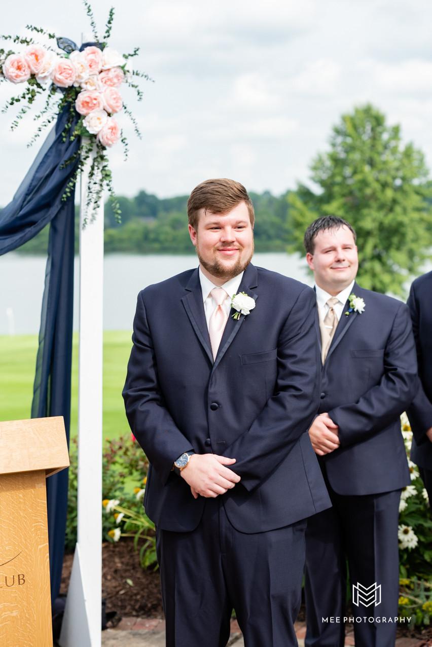 Groom in Navy tux watching his bride walk down the aisle