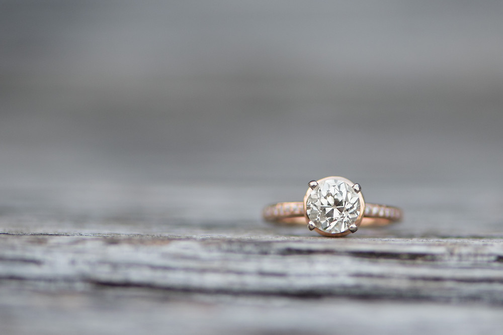 A detail shot of a round rose gold engagement ring sitting on a bench