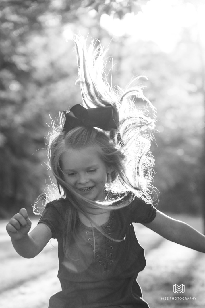 Black and while photo of a four year old girl jumping