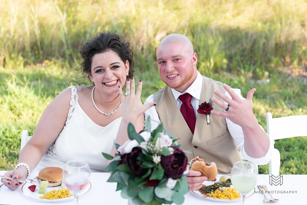 Bride and groom showing their wedding bands for a photo