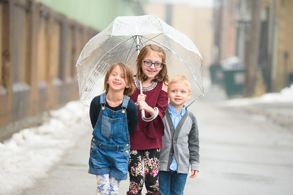 Siblings laughing in the rain under a clear umbrella.