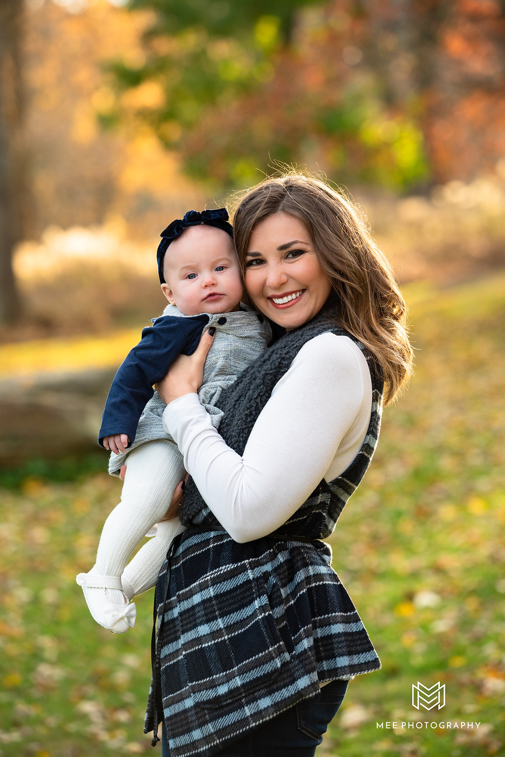 A mom holding her baby dressed in navy and white during their fall photo session