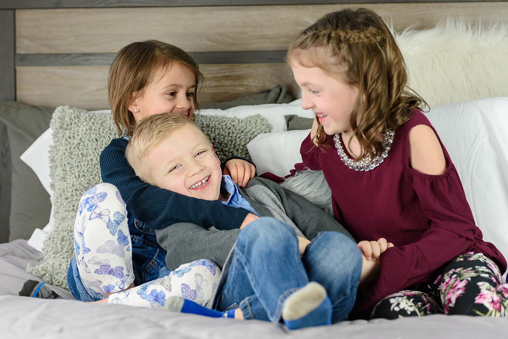 Two sisters tickling their little brother.