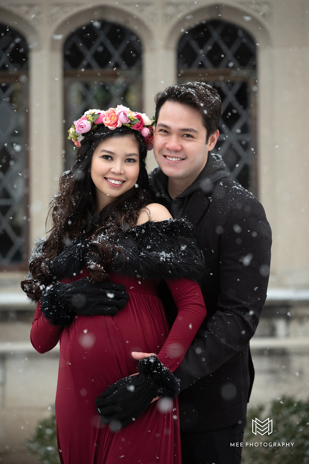 Couple winter maternity session in the snow with woman wearing red dress and flower crown at Hartwood Acres