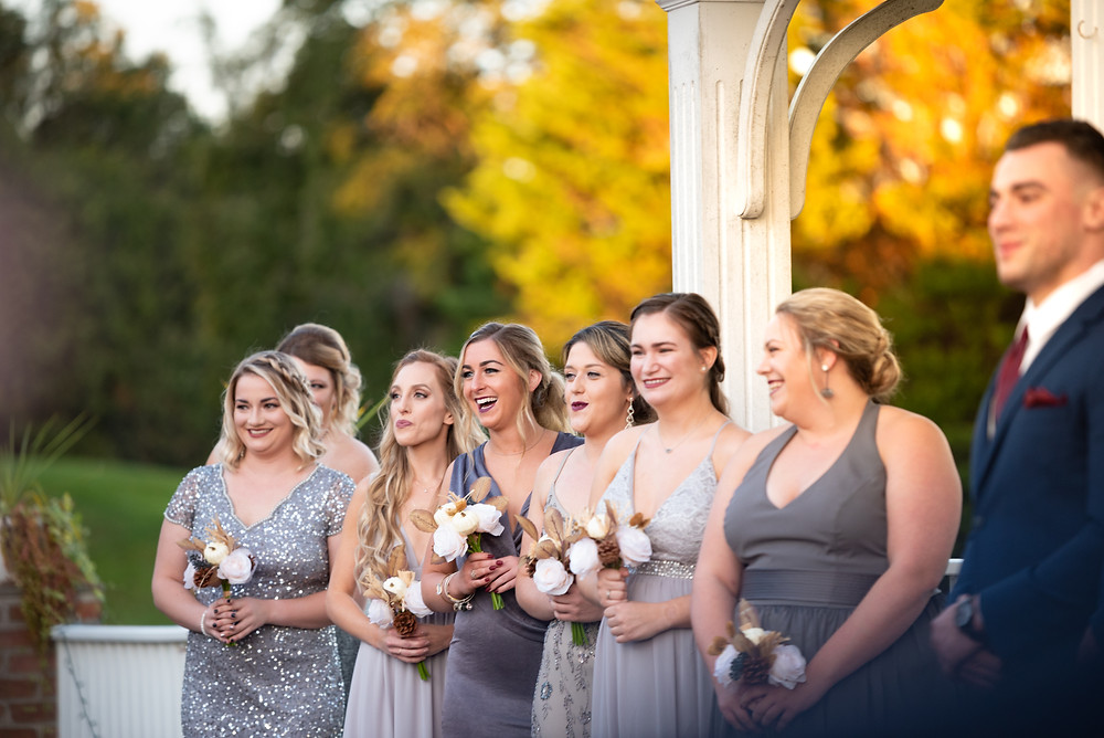 Bridesmaids laughing during an outdoor wedding ceremony at Morningside Inn in Frederick Maryland