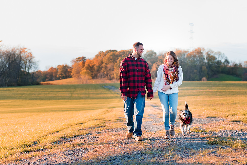 The couple and their dog walking through a field and laughing at sunset during their engagement session
