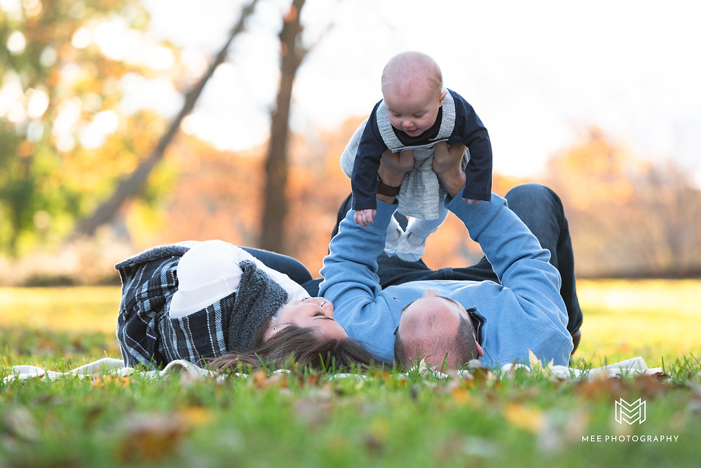 Parents laying on a blanket in the grass holding their baby in the air