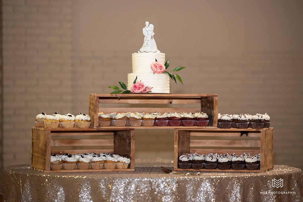 Rustic wedding cake and cupcakes displayed in pallets