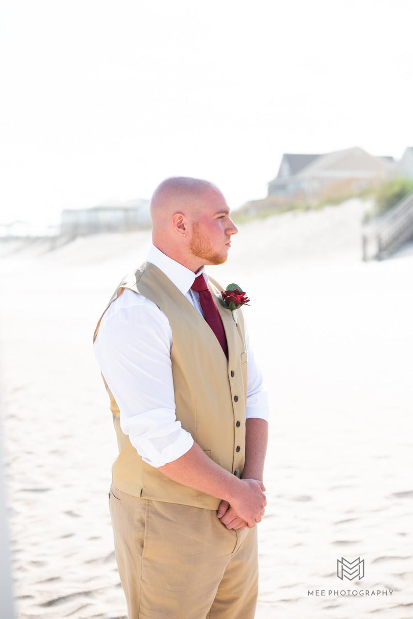Groom watching his bride walk down the isle on the beach