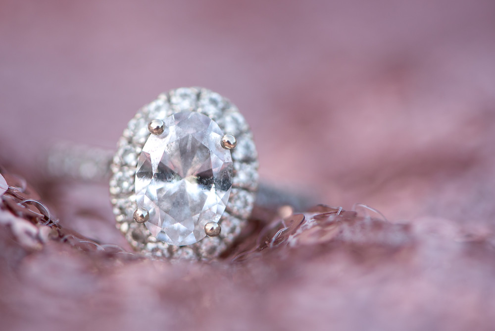 Macro shot of an oval diamond engagement ring with a single halo