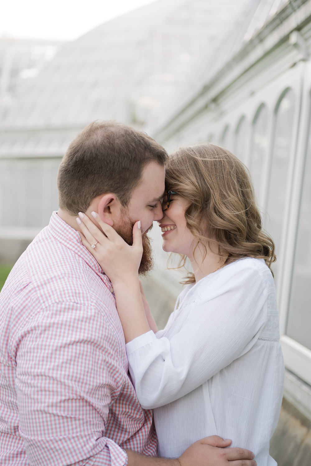 Couple embracing and laughing during their engagement shoot in Pittsburgh.