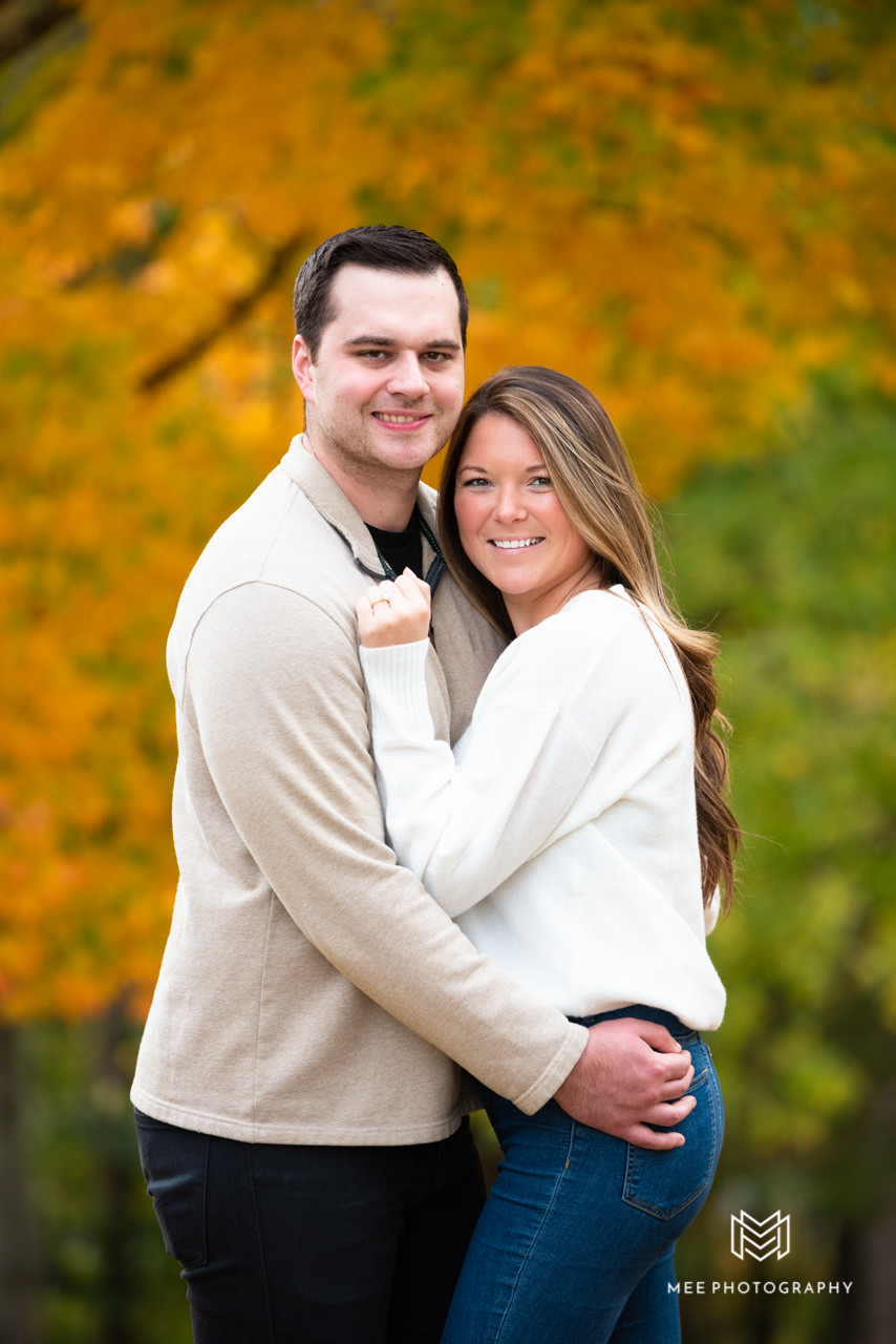 Engaged couple smiling at the camera with fall leaves in the background at Oglebay Park
