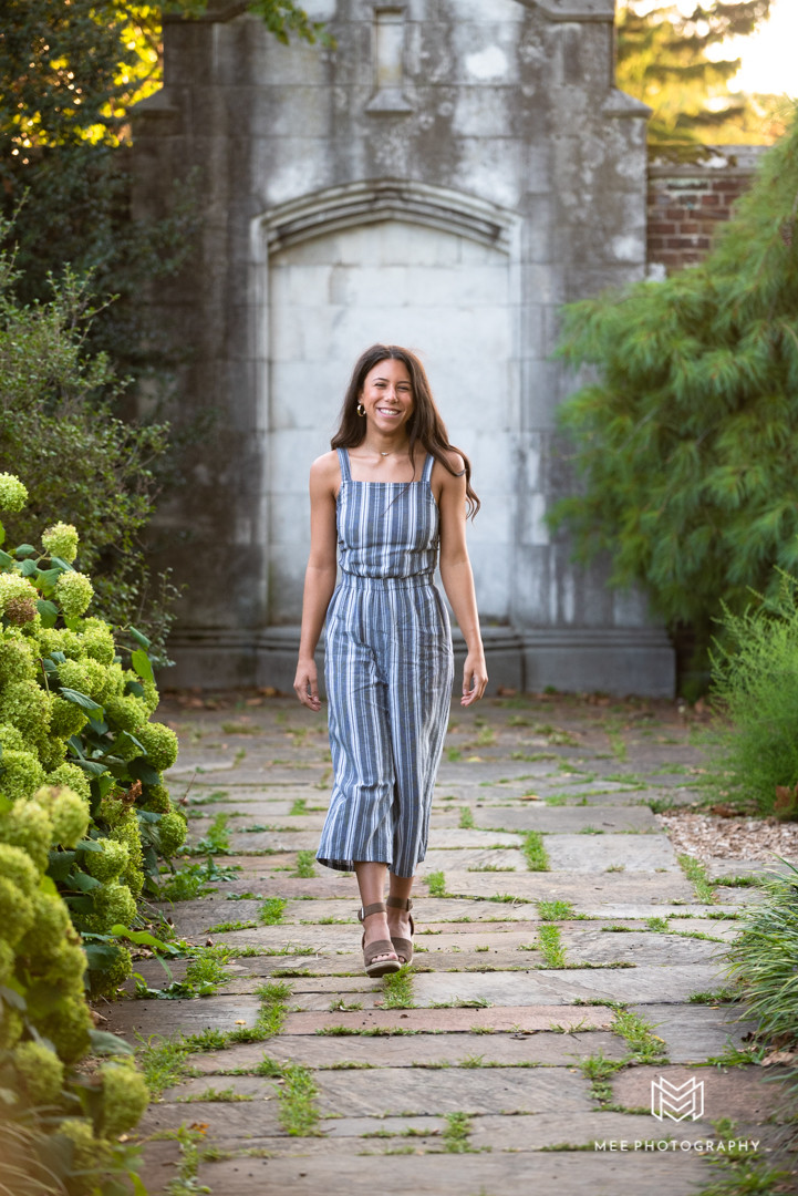 Senior girl walking and laughing wearing a gray and white striped jumpsuit during her senior photos