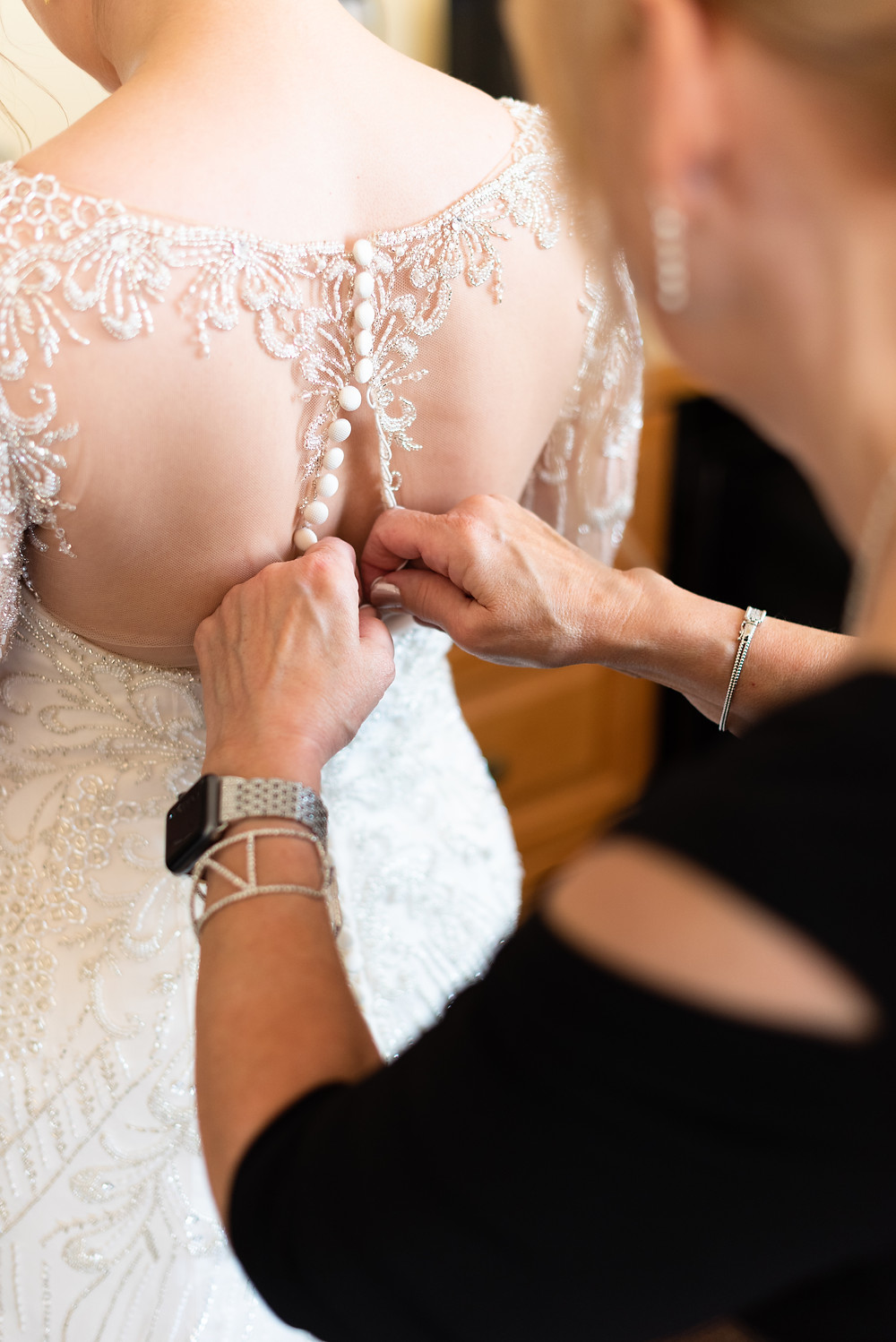 Mother of the bride buttoning the back of her daughter's wedding dress