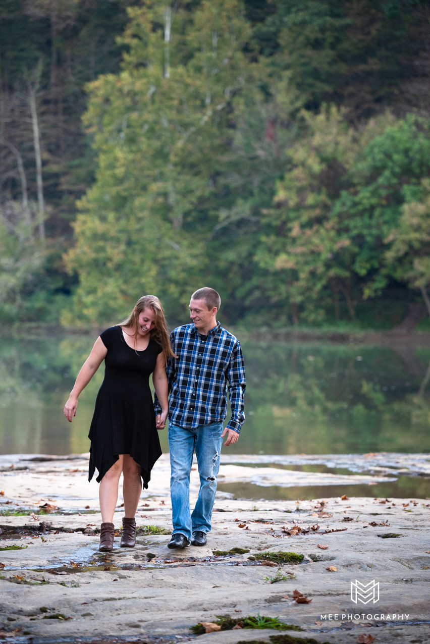 Couple walking and laughing with river and trees in the background
