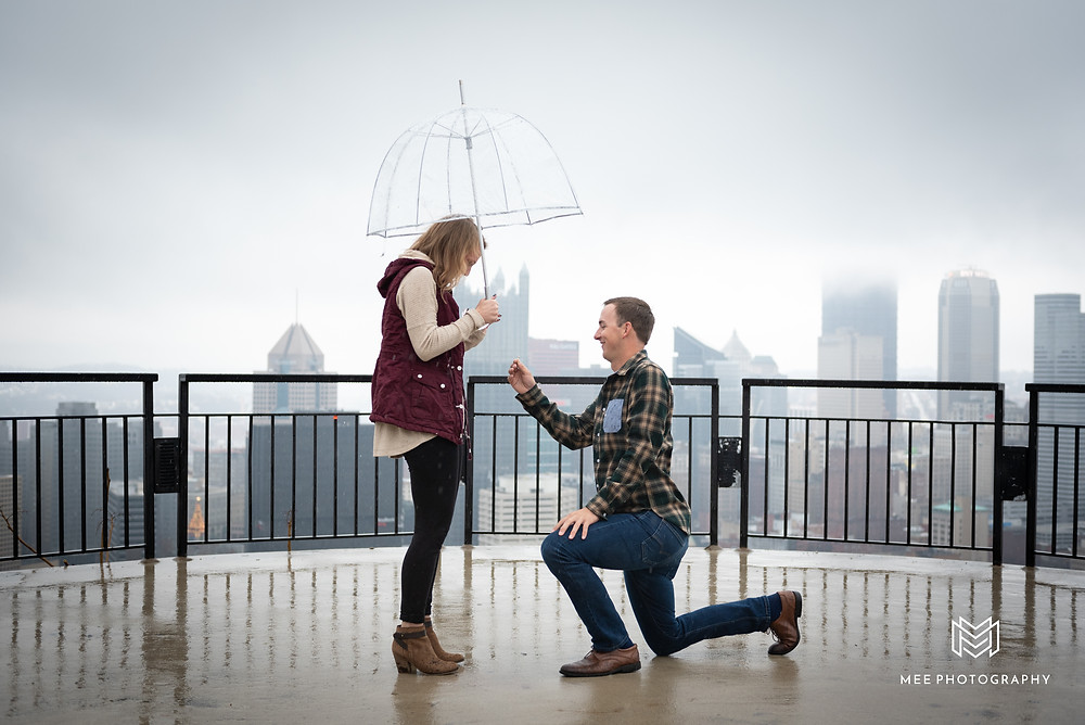 Pittsburgh proposal on Mount Washington in the pouring rain with clear umbrellas.