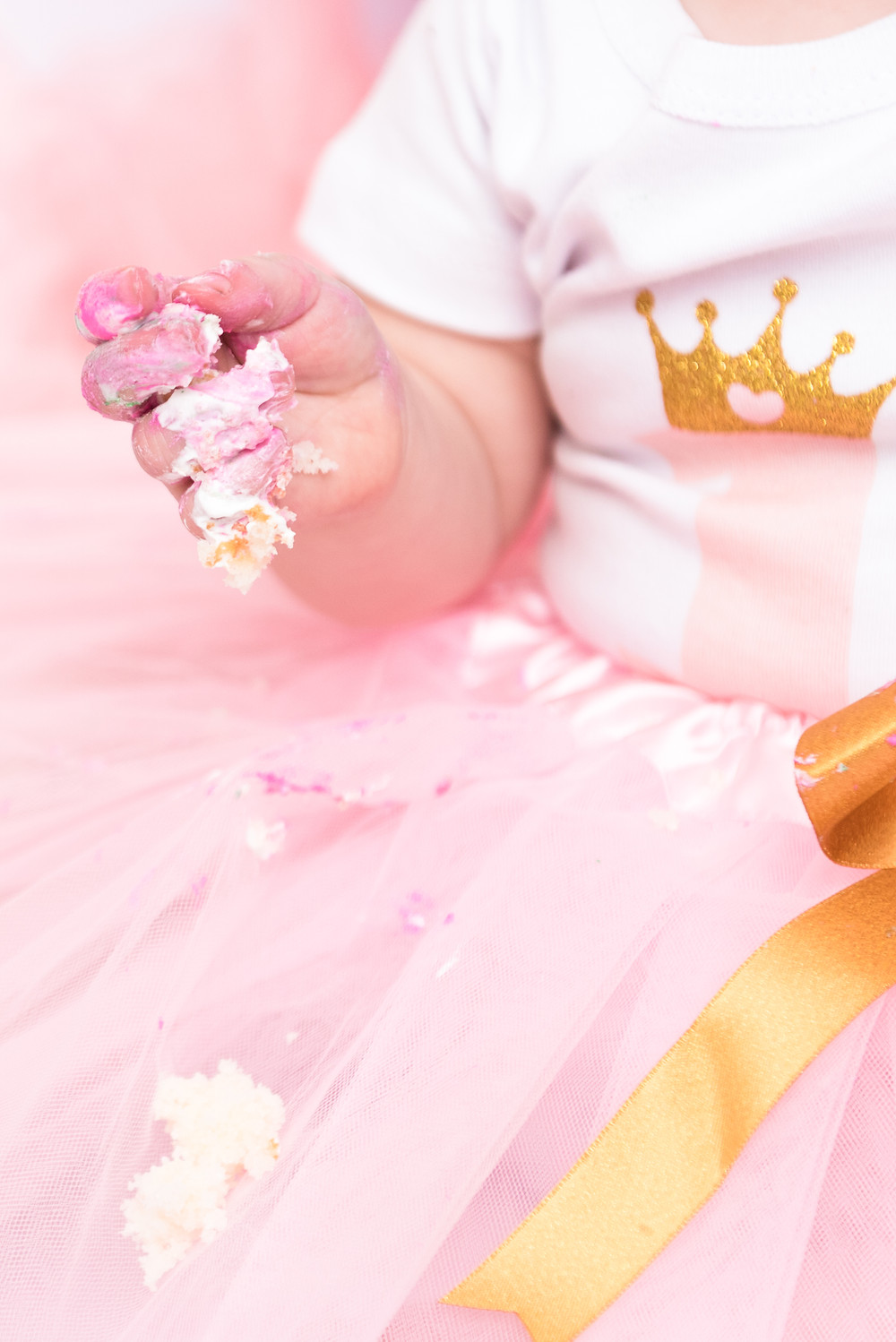 A detail shot of a baby's hand covered in frosting during her cake smash session near Pittsburgh.