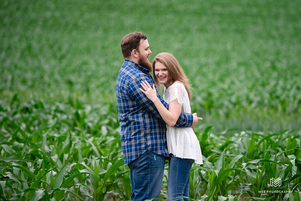Couple laughing during their save the dates photos in a corn field near Deep Creek Maryland