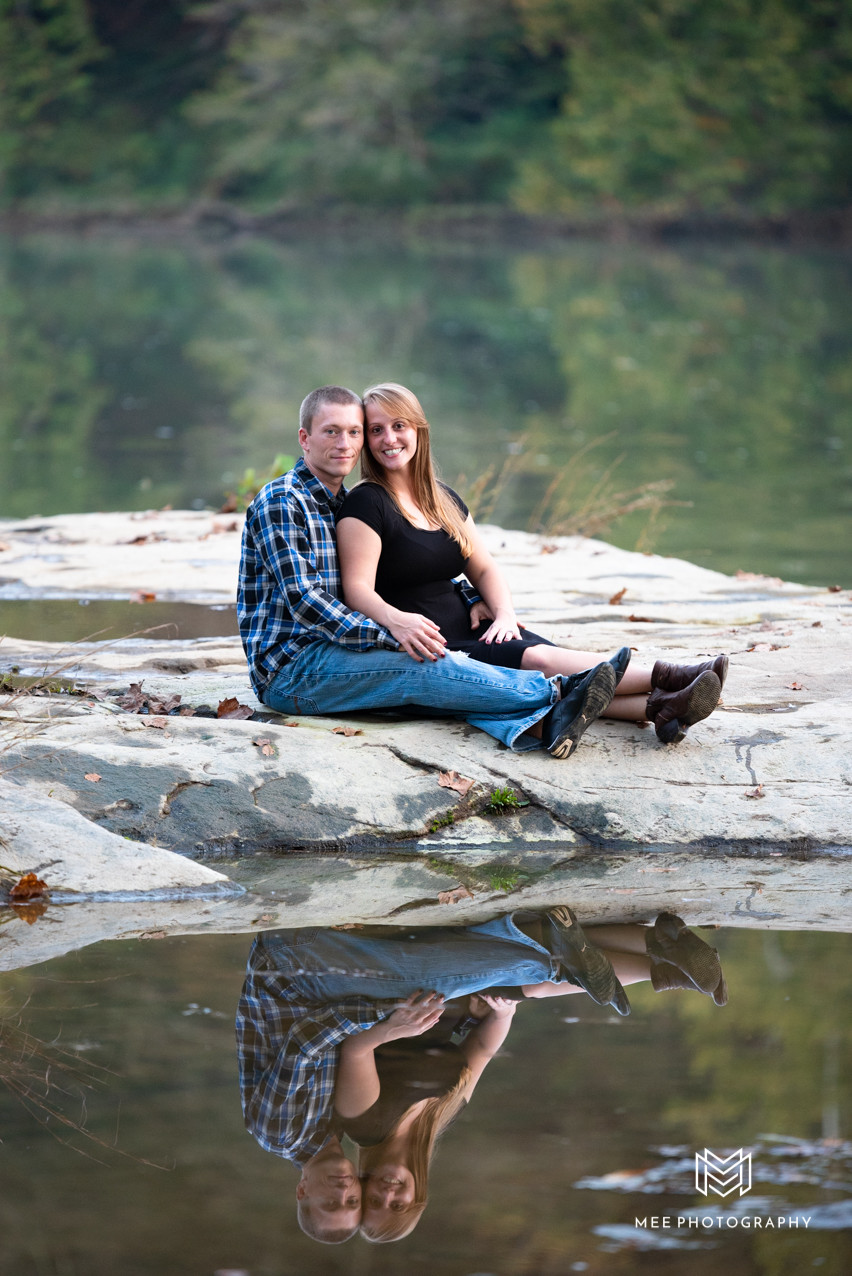 Couple sitting on rock with their reflection on the water at Valley Falls State Park