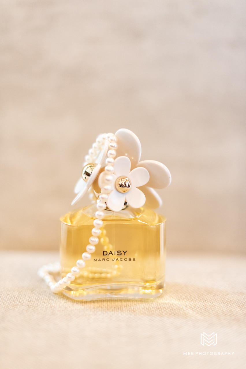 A bottle of Daisy perfume by Marc Jacobs and the bride's pearl necklace