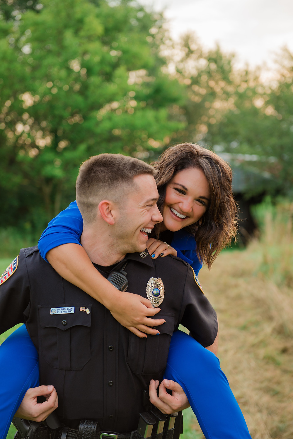 TA police officer holding his fiance on his back and laughing during their engagement session.