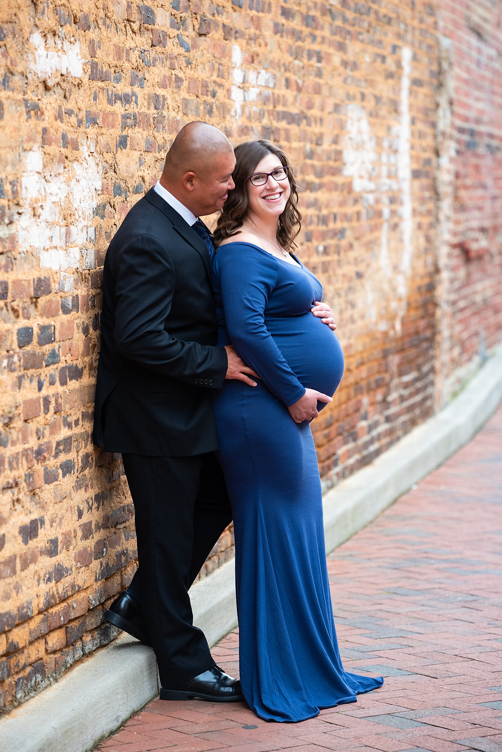 Couple's maternity photos in a blue dress against a brick wall in Hagerstown