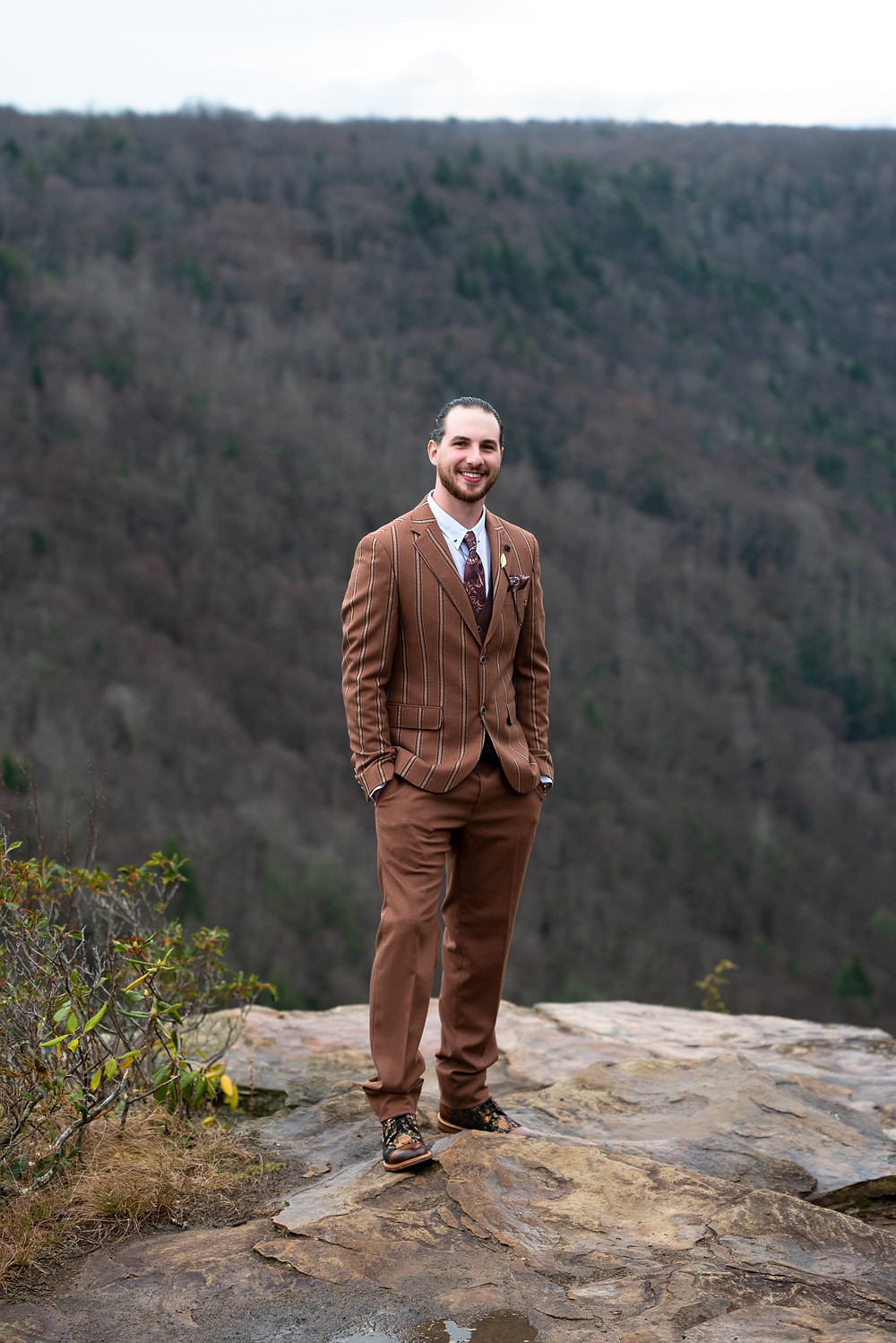 Groom wearing brown pinstripe suit on top of a mountain