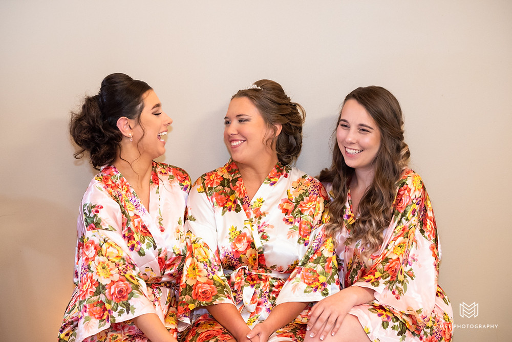 Bride and bridesmaids in flower robes before the ceremony