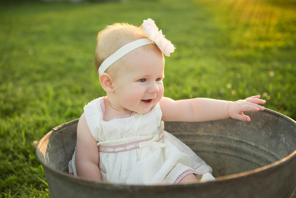 Baby sitting in metal tub outside during a photo shoot near Pittsburgh. She is wearing a ivory dress with a matching flower headband.