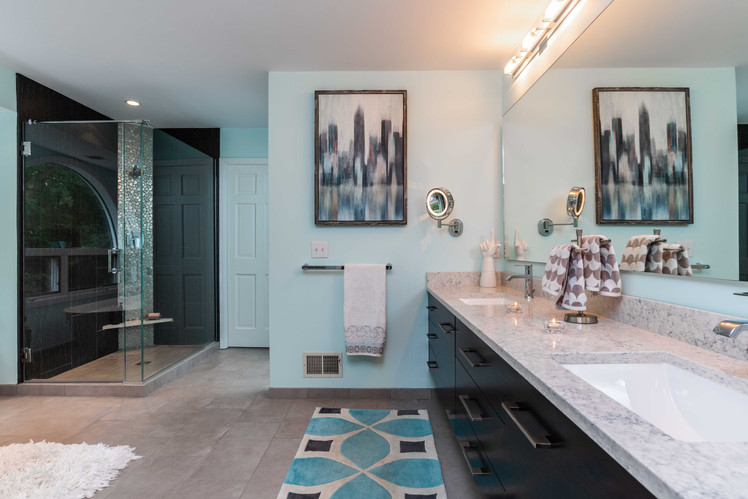 Contrasting dark and light tones and graphic punches create drama in this expansive bathroom