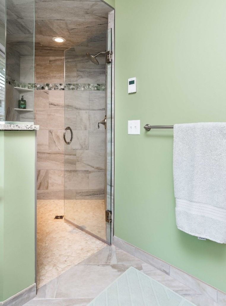 A barrier-free entry and unique pebble tile floor define this dreamy shower