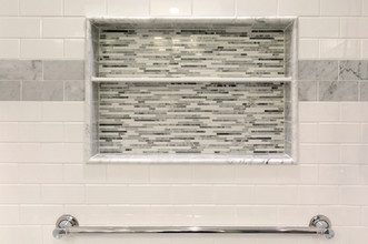 A beautiful use of ceramic tile and marble on in the tub/shower surround