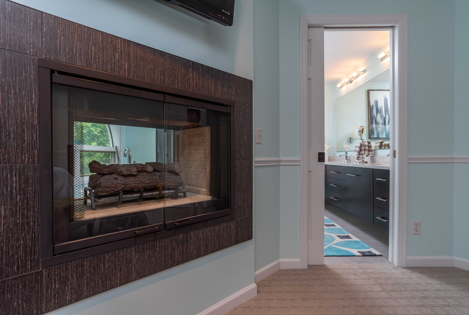 EDEN PRAIRIE TREETOP BATH:   The double-sided fireplace and doorway provide a glimpse into this colorful and comfortable bathroom