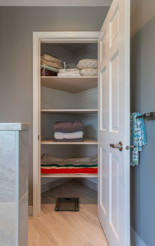 A spacious linen closet is tucked into the space once occupied by the shower