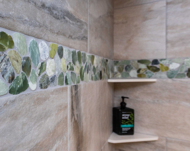 Beautiful beach glass pebble tile accents the shower walls