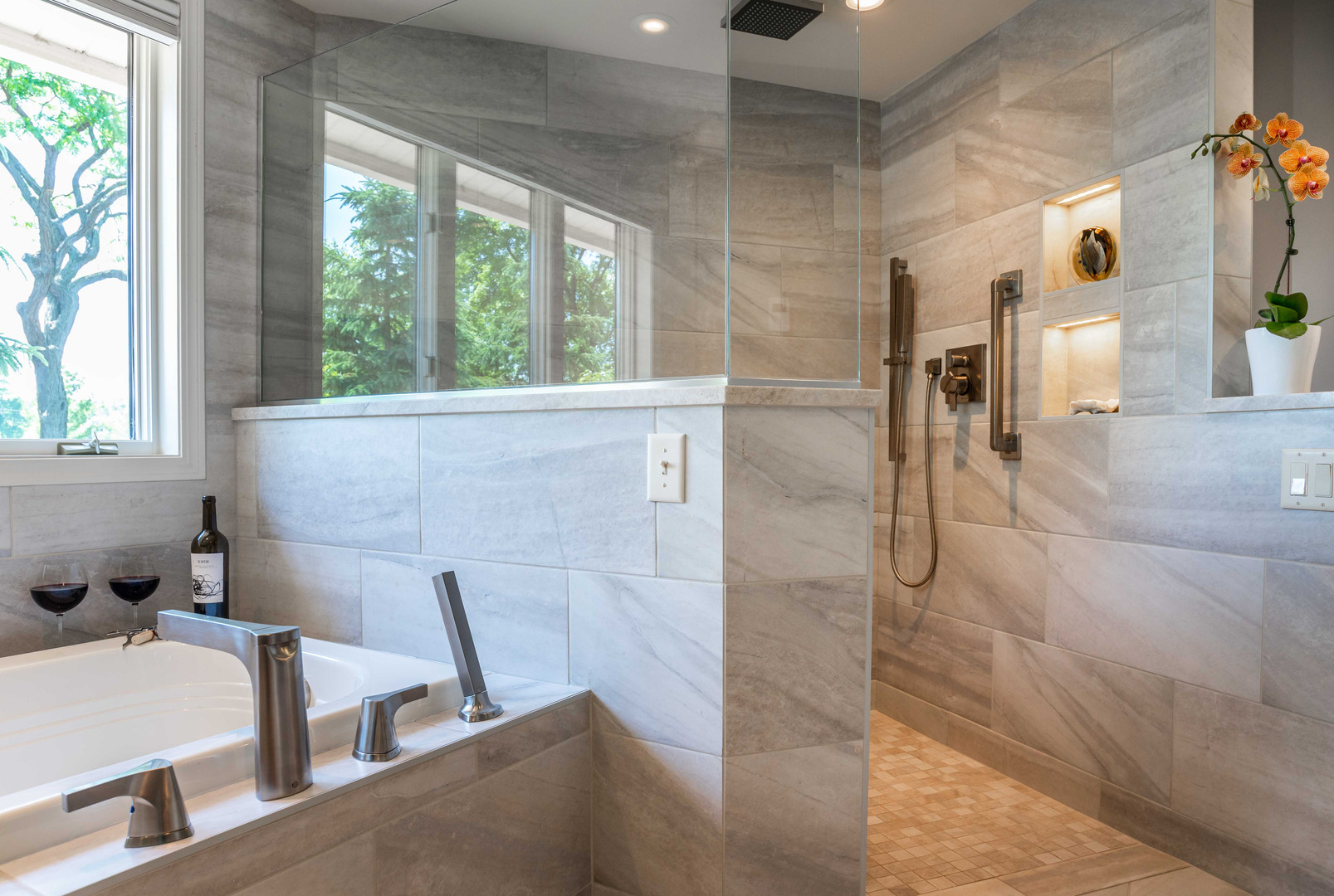 A luxury hotel-worthy shower features large scale, stone-look porcelain tile, a barrier-free entry, high-end fixtures and illuminated shampoo niches