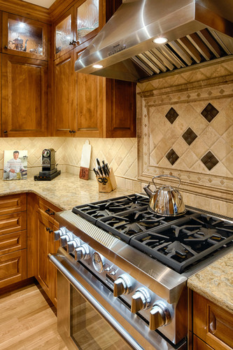 A standout feature of this kitchen is the stunning, Italian-inspired backsplash over the range