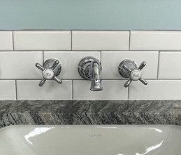 Our clients splurged on this vintage-inspired, wall-mounted vanity faucet to bring old world charm to their new bathroom