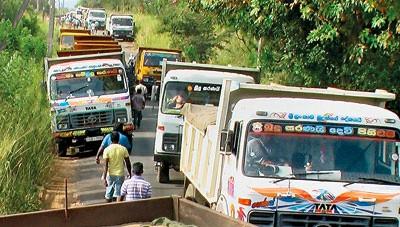Convoy of dump trucks transporting sand