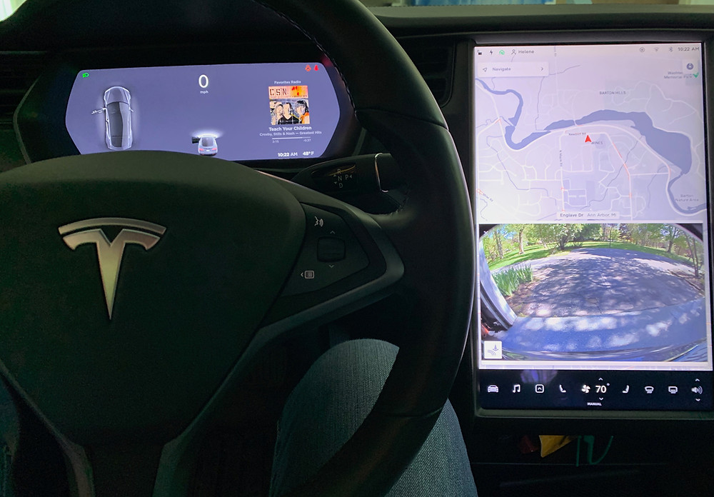Driver display of speed and car, infotainment screen with map and rear camera image.