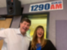 Tom and Helene in front of an 1290AM WLBY studio sign.